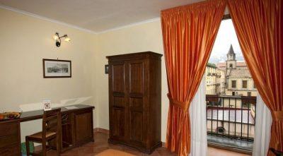 Ein Schlafzimmer mit Holzmöbeln und einem orangenen Vorhang, im Hintergrund ein Marktplatz - Übernachtung während einer individuellen Wanderung in Italien