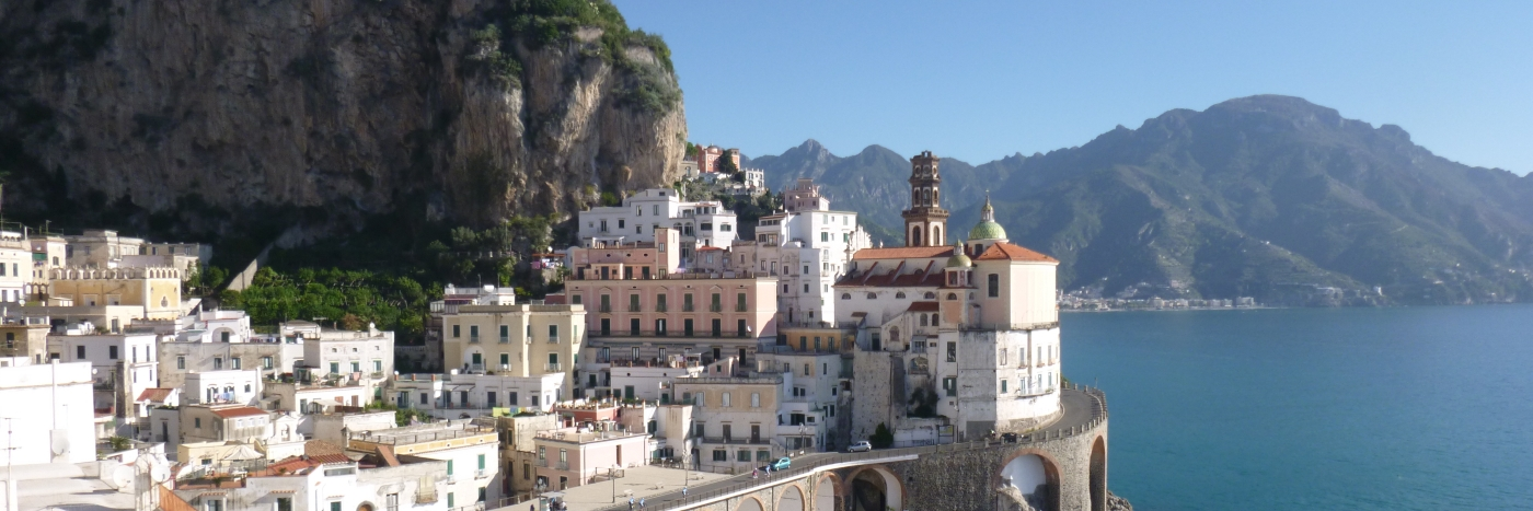 Blick auf zahlreiche helle Häuser an der Küste mit strahlenblauem Meer und Bergen im Hintergrund - gesehen auf einer individuellen Wanderung in Italien
