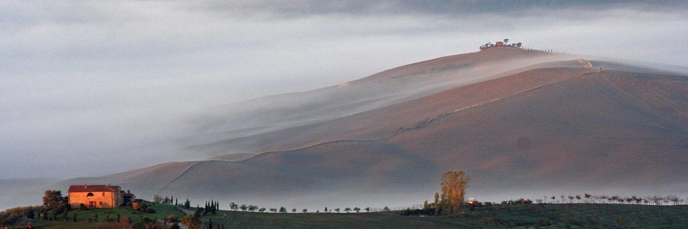 ein großer Berg in Nebel eingehüllt, im Vordergrund ein Haus umgeben von einer begrünten Landschaft - gesehen auf einer individuellen Wanderung in der Toskana