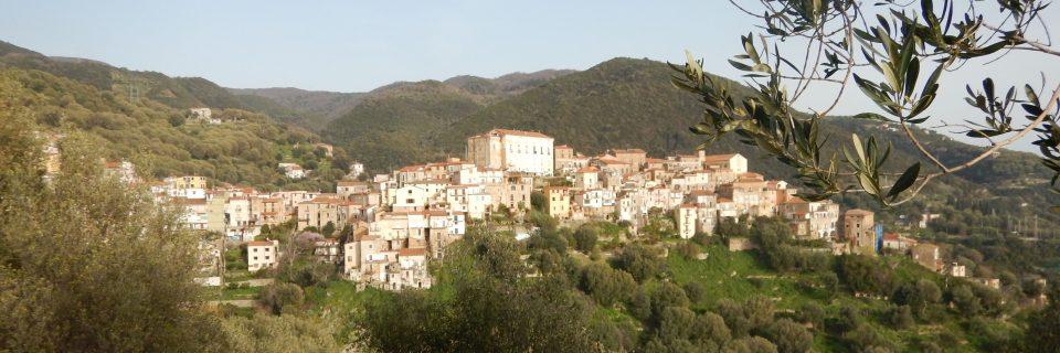 Mehrere Häuser umringt von Wäldern und Bergen - gesehen auf einer individuellen Wanderung in Süd-Italien