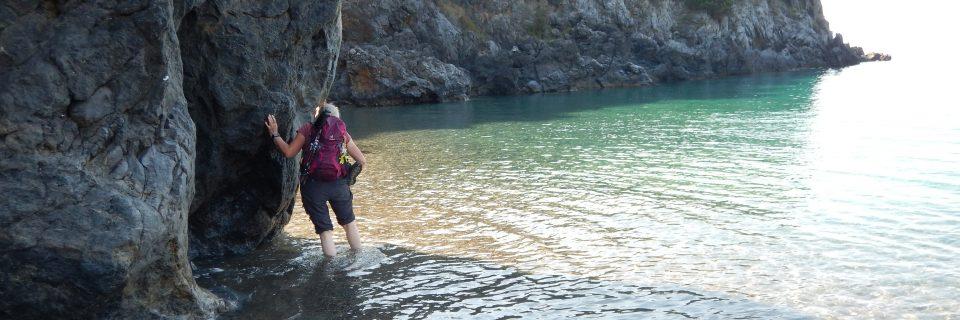 Eine Frau mit einem lila Rucksack steht mit den Füßen in klarem Wasser und stützt sich an einem Felsen ab - gesehen auf einer individuellen Wanderung in Süd-Italien