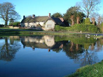 Blick über einen See auf ein Haus umgeben von einer Hecke und mehreren Bäumen - gesehen auf einer individuellen Wanderung in England