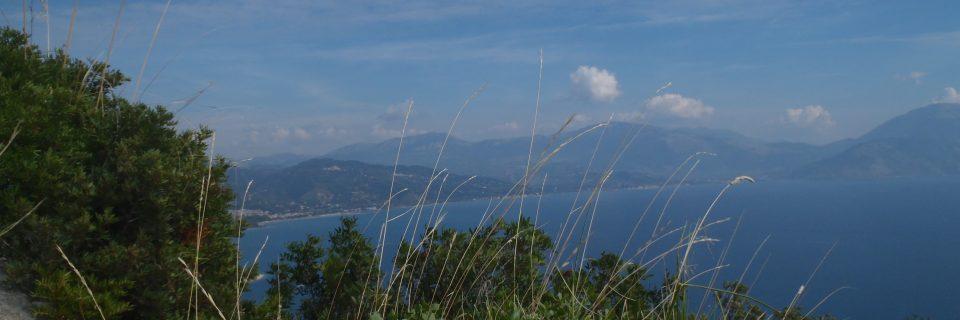 Ein großer, blauer See hinter verschiedenen Gräsern und Sträuchern - gesehen auf einer individuellen Wanderung in Süd-Italien