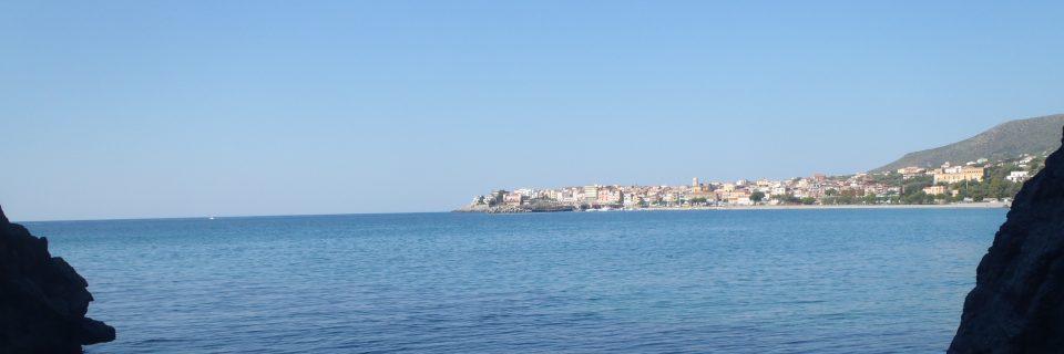 Strahlend blaues Wasser mit einem länglichen Fels am Horizont und blauem Himmel - gesehen auf einer individuellen Wanderung in Süd-Italien