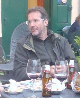Ein dunkel bekleideter Mann mit Brille sitzt vor einem gedeckten Tisch - Peter Hoogstaden hat die individuelle Wanderung in Süd-Italien mitentwickelt
