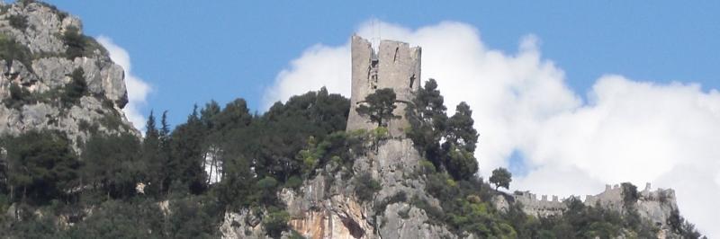 Blick auf eine steinerne Burgruine von mehreren Bäumen umgeben - gesehen auf einer individuellen Wanderung in Italien
