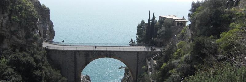 Blick auf eine steinerne Brücke über blauem Wasser, daneben mehrere Bäume - gesehen auf einer individuellen Wanderung in Italien