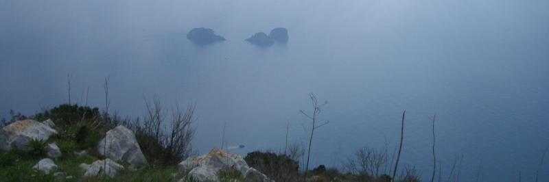 Blick von einer Grünlandschaft auf das vernebelte Meer - gesehen auf einer individuellen Wanderung in Italien