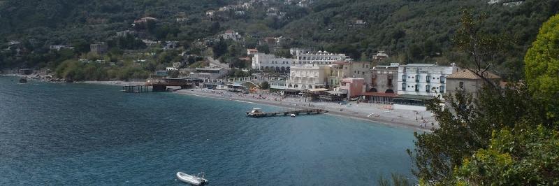 Blick vom Meer aus auf den Strand mit langem Steg und zahlreichen Gebäuden - gesehen auf einer individuellen Wanderung in Italien