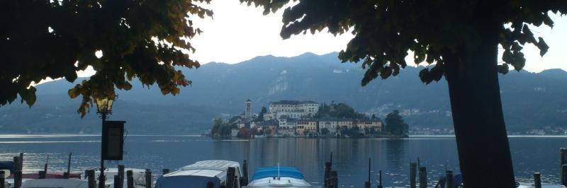 Blick vom Ufer über anliegende kleine Boote auf die Gebäude am anderen Ufer - gesehen auf der individuellen Wanderung am Lago Maggiore