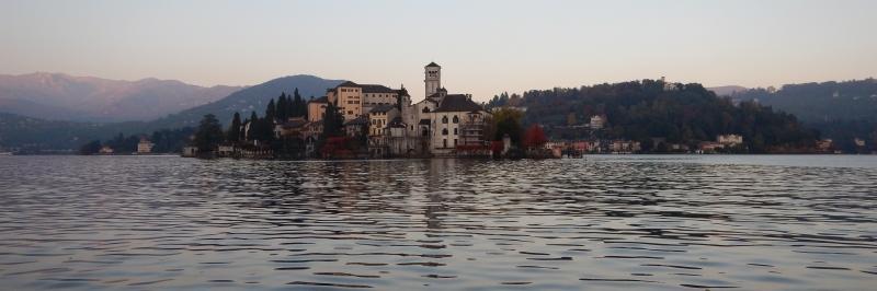 der Blick vom Wasser auf mehrere Gebäude mit einem hohen Turm - gesehen auf der individuellen Wanderung am Lago Maggiore