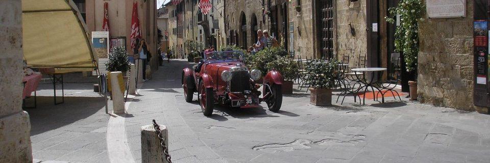 vor verschiedenen Häuserfassaden ein roter Oldtimer - gesehen auf einer individuellen Wanderung in der Toskana