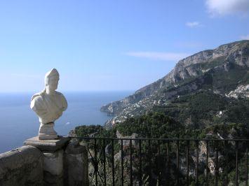Blick über ein Geländer mit weißer Büste auf das blaue Meer mit Bergen - gesehen auf einer individuellen Wanderung in Italien